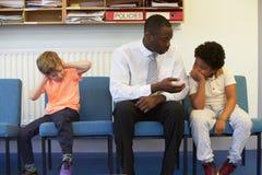Учитель разрешая проблему между 2 студентами школы Стоковые Изображения