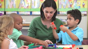 Учитель сидит с группой в составе дети используя набор конструкции сток-видео