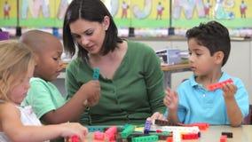Учитель сидит с группой в составе дети используя набор конструкции видеоматериал
