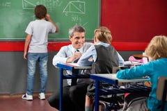 Учитель смотря школьницу пока заискивающ на Стоковые Фото