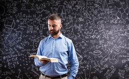 Учитель с книгой против большого классн классного с символами и formul Стоковые Изображения RF