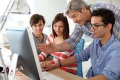 Учитель с студентами в классе используя компьютер стоковые изображения