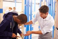 Учитель с студентом в замке класса плотничества подходящем Стоковое Изображение