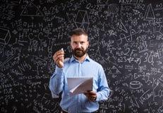 Учитель с тетрадью против большого классн классного с символами и fo Стоковая Фотография RF