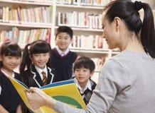 Учитель читая к ее студентам начальной школы стоковые изображения