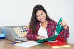 Учить кавказскую студентку с длинными темными волосами на столе на Стоковое Изображение RF