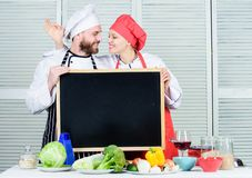 Учить с кулинарными специалистами Хелпер шеф-повара и повара показывая жестами ок на доске в варить школу Пары человека и женщины стоковые изображения