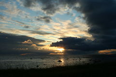 лучи заходящего солнца, облака над морем, живая природа севера Стоковая Фотография RF