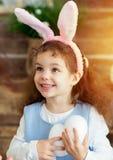 Уши зайчика милой девушки маленького ребенка нося на день пасхи Девушка держа корзину с покрашенными яичками Стоковые Изображения