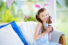 Уши зайчика милой маленькой девочки нося есть кролика пасхи шоколада Стоковые Фотографии RF