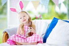 Уши зайчика милой маленькой девочки нося есть кролика пасхи шоколада Стоковое Изображение