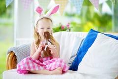 Уши зайчика милой маленькой девочки нося есть кролика пасхи шоколада Стоковые Фото