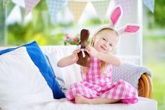 Уши зайчика милой маленькой девочки нося есть кролика пасхи шоколада Стоковая Фотография RF
