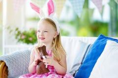 Уши зайчика милой маленькой девочки нося есть кролика пасхи шоколада Стоковая Фотография