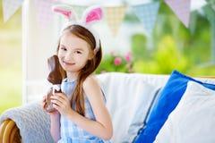 Уши зайчика милой маленькой девочки нося есть кролика пасхи шоколада Стоковое Фото