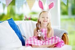 Уши зайчика милой маленькой девочки нося есть кролика пасхи шоколада Стоковые Изображения