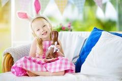 Уши зайчика милой маленькой девочки нося есть кролика пасхи шоколада Стоковые Изображения RF