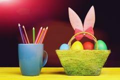 Уши зайчика пасхи девушек в розовом цвете стоя в корзине Стоковые Изображения