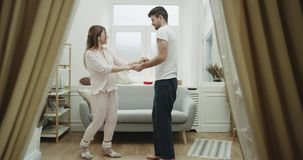 Уютная атмосфера в танцевать пар живущей комнаты романтичный в пижамах 4K видеоматериал