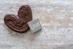Уютная деревянная предпосылка, с пальмой шоколада, кусок дерева со словом любит написанный, концепция любов, на день Валентайн стоковая фотография