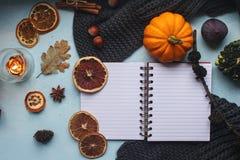 Уютная предпосылка осени, тетрадь, декоративные тыквы, высушенные апельсины, свеча, гайки, циннамон и листья осени Стоковое Изображение