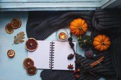 Уютная предпосылка осени, тетрадь, декоративные тыквы, высушенные апельсины, свеча, гайки, циннамон и листья осени Стоковое Фото