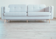 Уютная современная скандинавская софа стиля на настиле ламината дуба стоковое изображение