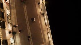 Уютная яркая улица с загоренными желтыми зданиями магазина и идя людьми сток-видео
