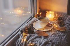 Уютное утро зимы или осени дома Горячий кофе с ложкой золота металлической, греет света одеяла, гирлянды и свечи Стоковые Фото