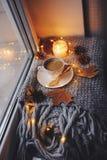 Уютное утро зимы или осени дома Горячий кофе с ложкой золота металлической, греет света одеяла, гирлянды и свечи Стоковые Изображения RF