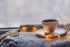 Уютное утро зимы или осени дома Горячий кофе с ложкой золота металлической, греет света одеяла, гирлянды и свечи Стоковое Изображение