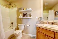 Уютный античный интерьер ванной комнаты в белых тонах с полками на стене Стоковое фото RF