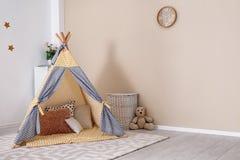Уютный интерьер комнаты детей с шатром и игрушками игры стоковые изображения