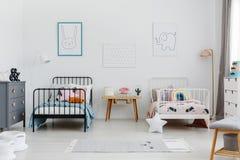 Уютный интерьер спальни для отпрысков 2 кровати, одна белизна, одно bla стоковое изображение