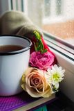 Уютный натюрморт: кружка горячих чая, книг и цветков с теплой шотландкой на windowsill Дождливый день снаружи Чтение, осень и зим стоковые изображения rf