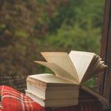 Уютный натюрморт осени: чашка горячего кофе и раскрытой книги на винтажном windowsill и дожде снаружи Осень афоризмов дождь стоковые изображения