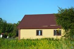 Уютный дом кирпича с экстерьером крыши металла дом слободская Стоковое фото RF