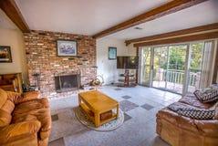 Уютный семейный номер с кожаными креслами и дверями сползая стекла Стоковая Фотография RF