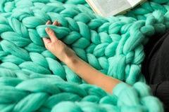 Уютный состав, крупный план книги чтения женщины на шерстях p merino Стоковые Изображения
