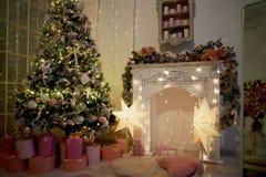 Уютный яркий интерьер в стиле Нового Года Декоративный камин, света, рождественская елка с подарками Новый Год торжества стоковые фото
