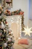 Уютный яркий интерьер в стиле Нового Года Декоративный камин, света, рождественская елка с подарками Новый Год торжества стоковые изображения