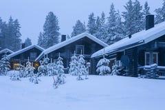 3 уютных деревянных дома с рождественской елкой в фронте расположенном в спокойном живописном нордическом лесе Стоковое Изображение RF