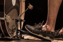 ударный инструмент, басовый барабанчик с педалью на деревянной доске с черной предпосылкой, ногой людей Стоковое фото RF