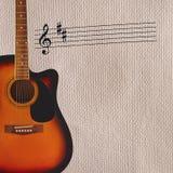 Ударяйте и акустическая гитара sunburst на левой стороне грубой предпосылки картона Стоковое Изображение