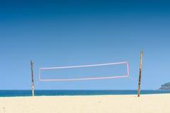 Ударять сеть шарика на тропическом пляже с голубым небом в летнем дне Стоковое Изображение