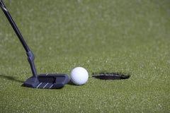 Удар, загоняющий мяч в лунку гольфа на зеленом поле Стоковые Фотографии RF