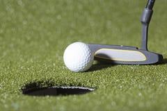 Удар, загоняющий мяч в лунку гольфа на зеленом поле Стоковые Изображения