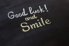 Удача и улыбка - написанный текст стоковые изображения