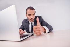 Удача к вам Усмехаясь африканский бизнесмен сидя на столе Стоковое Фото