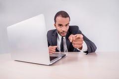 Удача к вам Усмехаясь африканский бизнесмен сидя на столе стоковое изображение rf